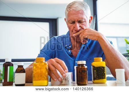 Senior man holding medicine in a retirement home