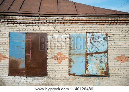 old brick house with boarded up windows