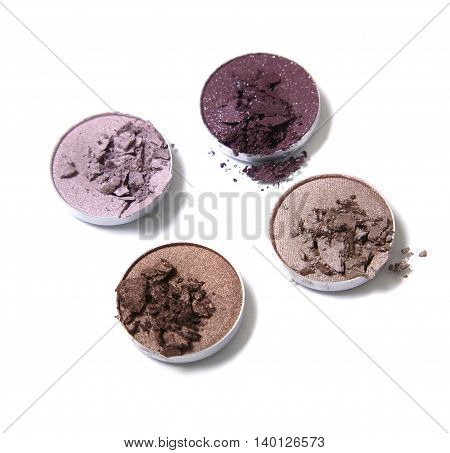 Smashed neutral and pink toned eye shadow make up pots isolated on a white background