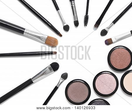 Assorted make up brushes and eyeshadow pots isolated on a white background and arranged to from a circle page frame