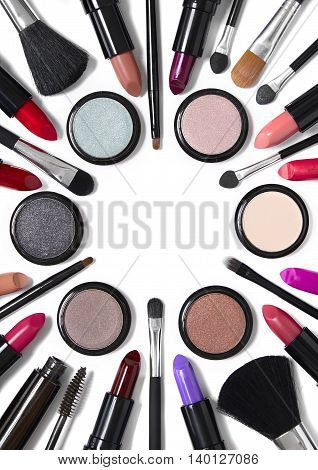 Assorted cosmetic beauty products and make up brushes isolated on a white background and arranged to form a circle shaped page frame