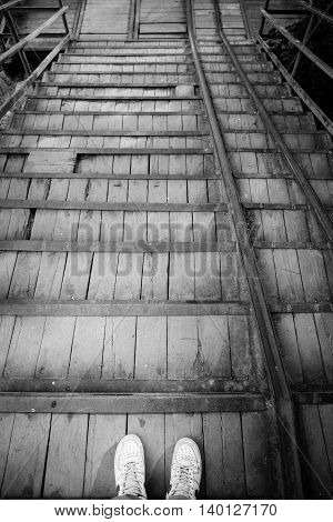 Male legs stand on old wooden and metal stairs