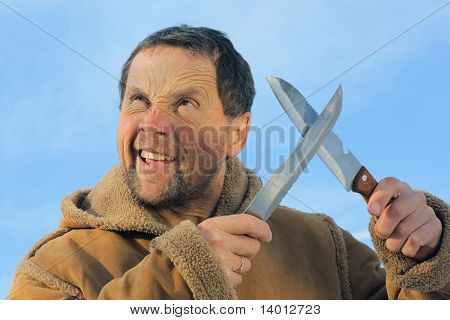 Man with crazy face and two knifes