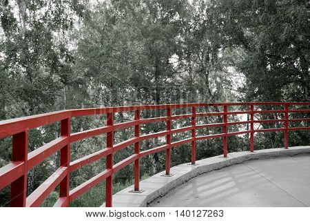 red fence on the park, around forest