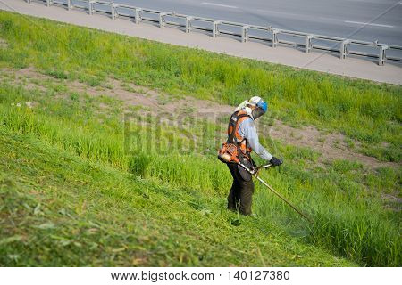 The worker in a uniform and mask cuts off a thick grass