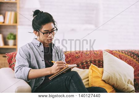 Creative young man drawing in his album