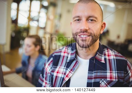 Portrait of businesman with female colleague in background at creative office