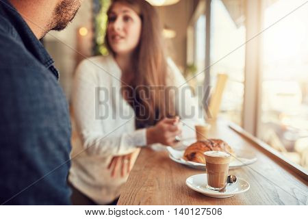 Cup of coffee and food on table with couple talking in background at cafe.