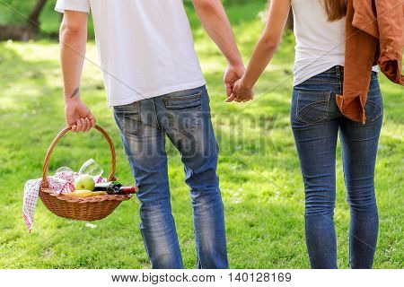 Couple in love walking through nature holding hands and carrying a picnic basket