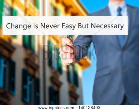 Change Is Never Easy But Necessary - Businessman Hand Holding Sign