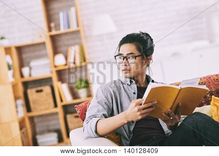 Portrait of handsome Asian man sitting on sofa with a book