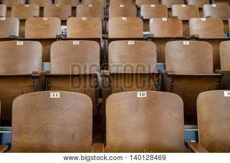 Antique Wood Auditorium Seat Backs Straight on View with two chairs in front