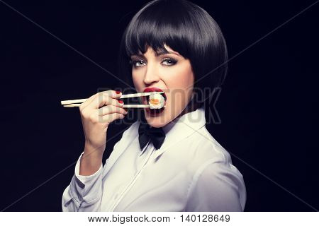 Sexy waiter with red lips and nails eating sushi on black background