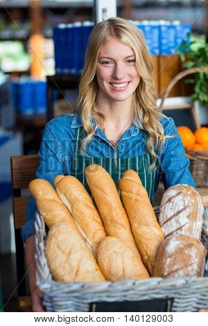 Portrait of smiling woman holding a basket of baguettes in supermarket