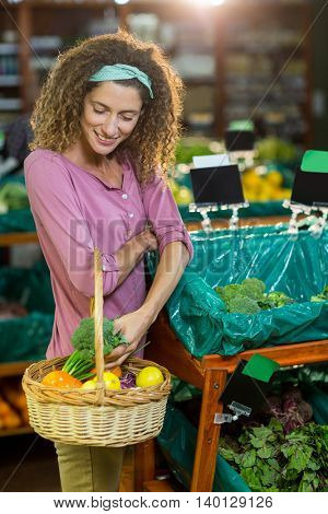 Smiling woman buying vegetables in organic section of supermarket