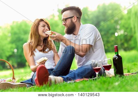 Couple in love sitting on a picnic plaid in a park eating sandwiches drinking wine and enjoying the day