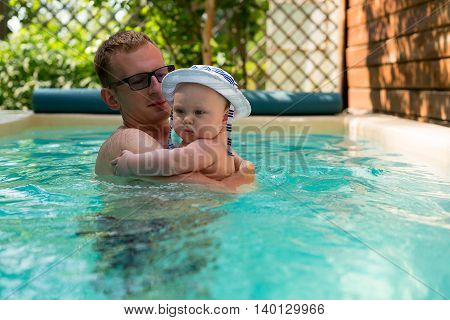 father and little son in a panama hat swimming in the pool