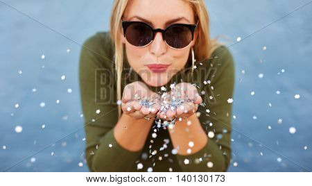 Attractive Young Woman Blowing Glitters