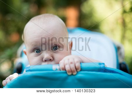 cute bald baby peeking out of a stroller