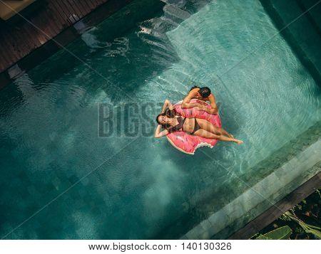 Couple Relaxing On Donut Floatie In Resort Pool