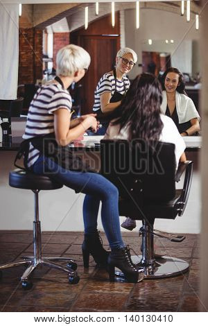 Smiling hair stylist sitting with client at the hair salon