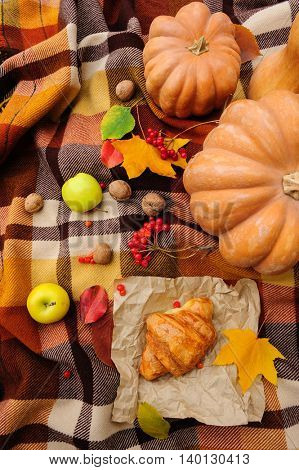 Romantic autumn still life with blanket, cake, pumpkins, croissant and leaves, top view