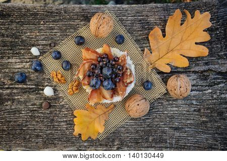 Romantic autumn still life with blackthorn berries in blue bowl and bagel on wooden board
