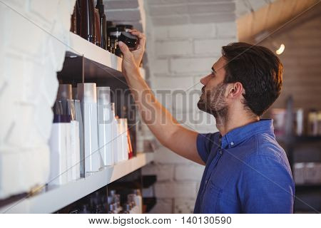 Male hair dresser selecting gel from shelf at a salon