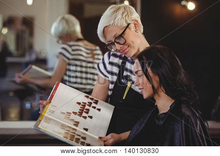 Woman selecting a hair color with stylist at the hair salon