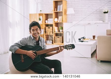 Portrait of young Vietnamese man practicing playing guitar at home