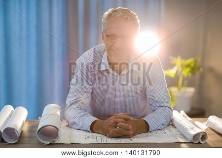 Portrait of man sitting with blueprint at his desk in the office