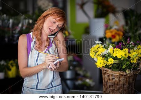 Female florist taking an order on mobile phone at the flower shop