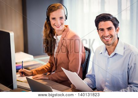 Portrait of businessman and businesswoman smiling at office