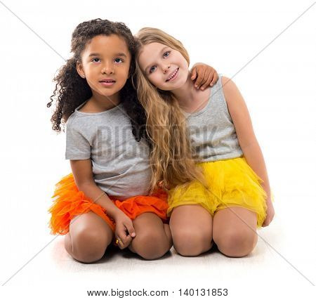 two little smiling girls-friends with different complexion sitting on the floor isolated on white background