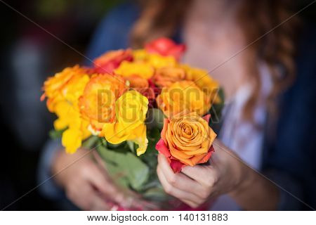 Female florist holding bunch of flowers in the flower shop
