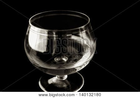 Shot glass with alcohol in monochrome execution. A shot glass with alcohol on a black background. Material glass. Liquid. Indoors. Monochrome. Horizontal format.