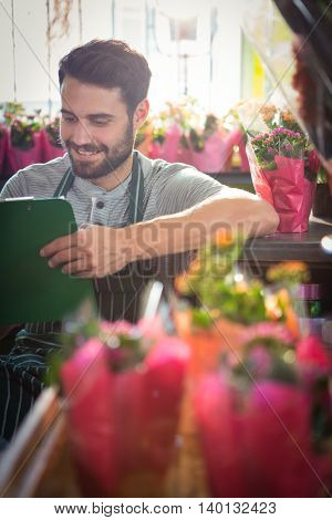 Male florist writing and making notes at his flower shop