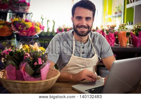 Portrait of male florist using laptop at his flower shop