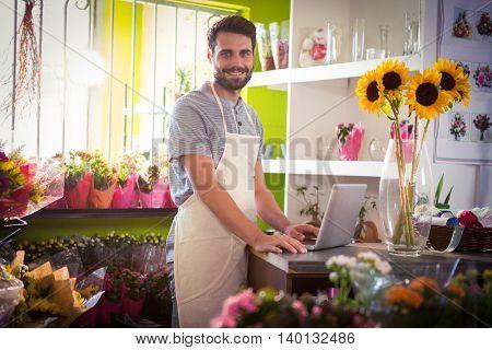 Portrait of male florist using laptop at his flower shop