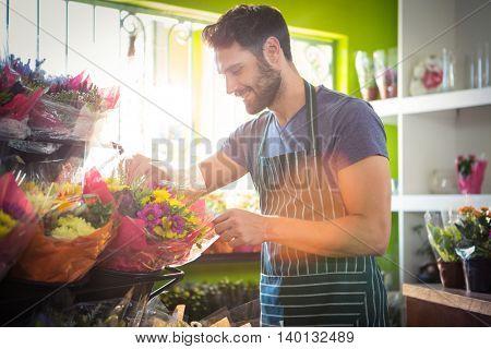 Male florist arranging bouquet of flower at his flower shop