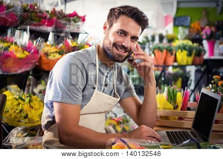 Portrait of male florist talking on mobile phone while using laptop at his flower shop