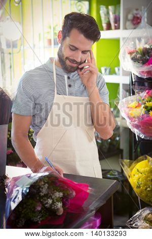 Male florist noting order while talking on mobile phone at his flower shop