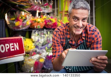 Portrait of male florist using digital tablet at his flower shop
