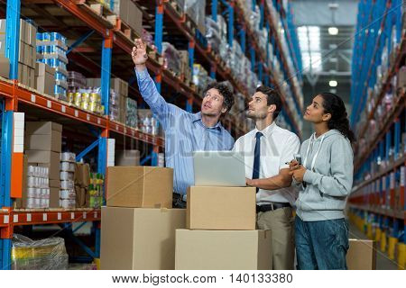 Worker team looking goods on a shelf in a warehouse