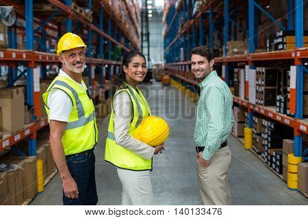 Portrait of manager and workers are standing and smiling to the camera in a warehouse