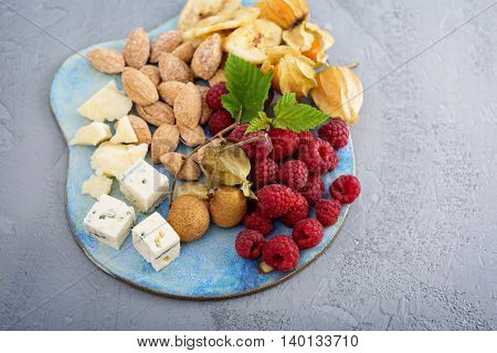 Fruit and nuts snack and cheese board including almonds, raspberry, blue cheese and parmesan