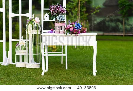 Vintage wedding decoration with white table flowers and parrot cage.