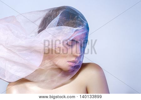 Beautiful Portrait Of A Cute Girl With Developing Cloth On His Head On Gray Background