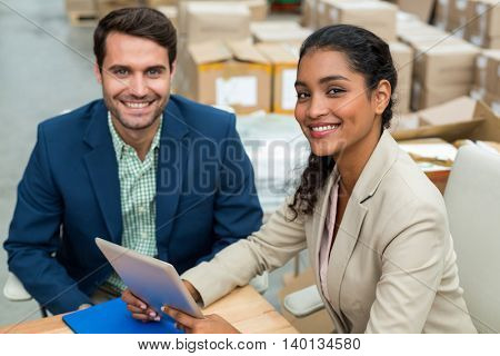 Portrait of happy managers are posing and looking the camera during work in a warehouse