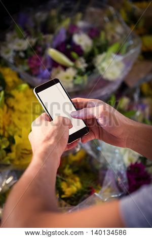 Male florist text messaging on mobile phone at his flower shop